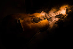 Music concept. Acoustic guitar isolated on a dark background under beam of light with smoke with copy space. Guitar Strings, close. Up. Selective focus. Fire Royalty Free Stock Image