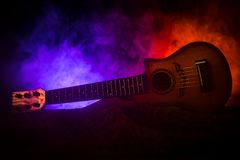 Music concept. Acoustic guitar isolated on a dark background under beam of light with smoke with copy space. Guitar Strings, close. Up. Selective focus stock images