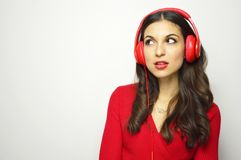 Music concept. Attractive girl with red headphones and red dressed start listening to music and looking on the side on white backg. Round with copy space stock photo