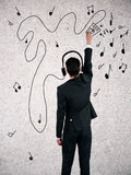 Music concept. Back view of young businessman with creative sketchings of headphones, player and musical notes. Music concept Stock Photography