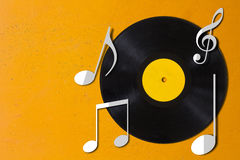 Music Concept Background. Music concept, record and note music on yellow vintage background Stock Image