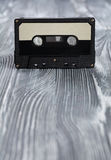 Music concept. Black audio cassette on the gray wooden background. Royalty Free Stock Photo