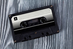 Music concept. Black audio cassette on the gray wooden background. Vintage, retro style. Soft focus. Stock Photos