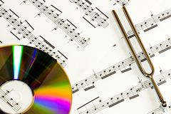 The music concept. CD disc and pitchfork on the notes background. The symbol of classical music and creativity Stock Photography