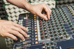 Detail of the hands of a man manipulating a mixing desk. Music concept. Detail of the hands of a man manipulating a mixing desk royalty free stock photo