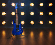 Music concept. Electric guitar standing on the wooden floor near Stock Photos