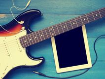 Vintage guitar with earphones on wood Royalty Free Stock Photography