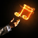 Music concept presented by fire burning icon. Close up of person hand and fire music symbol on dark background Royalty Free Stock Photography