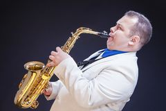Expressive Mature Caucasian Male Saxophone Player Posing in White Suite. Music Concepts. Expressive Mature Caucasian Male Saxophone Player Posing in White Suite Royalty Free Stock Photography