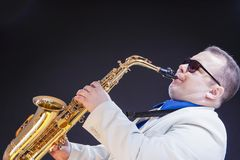 Music Concepts. Expressive Mature Playing Saxophonist Posing In. Sunglasses With Sax. Against Black Background. Horizontal composition Royalty Free Stock Photo