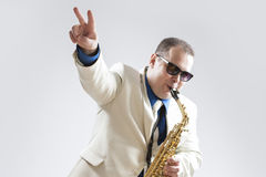 Music Concepts and Ideas. Portrait of Hadnsome Male Saxophone Player Showing V Sign Whilst Playing Stock Photo