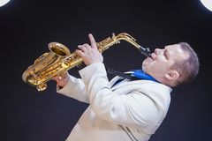 Music Concepts. Mature Caucasian Male Saxophonist. Music Concepts. Mature Caucasian Male Saxophone Player Posing in White Suite With Sax. Against Black Royalty Free Stock Image
