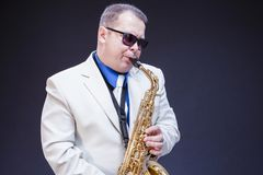 Music Concepts. Portrait of Expressive Playing  Mature Male Saxo Player. Music Concepts. Portrait of Expressive Playing  Mature Male Saxophonist Posing In Royalty Free Stock Photo