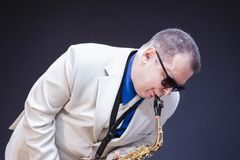 Music Concepts. Portrait of Expressive Playing  Mature Male Saxophonist. Posing In Sunglasses With Sax. Against Black Background. Horizontal Image Stock Images
