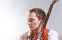 Music Concepts. Portrait of Young Male Guitar Player Against Gra Royalty Free Stock Photo