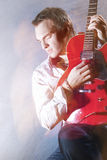 Music Concepts. Portrait of Young Male Guitar Player Performing Stock Photos