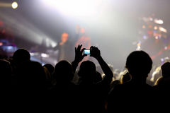 Music concert with audience and man doing photo. Music concert with audience and lights from the stage Royalty Free Stock Photo
