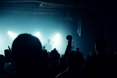 Music concert crowd, people enjoying live rock performance. Music concert fans crowd, people at popular live rock performance, hands in the air, selective focus Royalty Free Stock Image