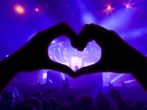 Music concert, hands raised in the shape of the heart for the music, blurred crowd and artists on stage in the background. With blue spotlights Royalty Free Stock Images