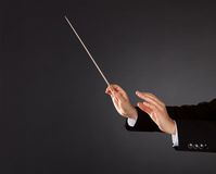 Music conductor with a baton. Closeup of the hands of a music conductor with a baton against a dark studio background with copyspace Stock Photo