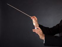 Music conductor with a baton. Closeup of the hands of a music conductor with a baton against a dark studio background with copyspace Royalty Free Stock Images