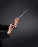 Music conductor with a baton. Closeup of the hands of a music conductor with a baton against a dark studio background with copyspace Royalty Free Stock Photos
