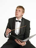 Music conductor in creation process. Young music conductor with score and baton Royalty Free Stock Photos