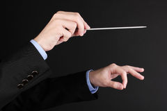Music conductor hands with baton. On black Royalty Free Stock Photo