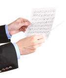 Music conductor hands with baton and notes. Over the white Royalty Free Stock Images