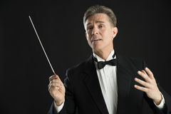 Music Conductor Looking Away While Directing With His Baton. Mature male music conductor looking away while directing with his baton against black background Royalty Free Stock Photo