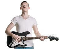 Music and creativity. A handsome young man in a T-shirt is holding an electric guitar. Horizontal frame. Music and creativity. A handsome young man in a T-shirt Royalty Free Stock Photo