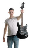 Music and creativity. A handsome young man in a T-shirt holds out an electric guitar in his hand. Play it. Horizontal frame. Music and creativity. A handsome stock images