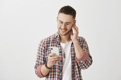 Music describe feelings. Studio shot of attractive caucasian guy in glasses looking at screen of smartphone, picking. Song to listen, wearing earphones and Royalty Free Stock Photography