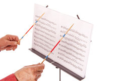 Music director with baton and sheet stand. Conductor with baton directing melody from music sheet stand Royalty Free Stock Photography