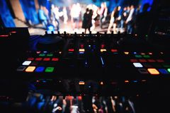 Music DJ Desk with blurred background of dance floor with dancing people in night club. Music DJ Desk with blurred background of the dance floor with dancing Royalty Free Stock Photo