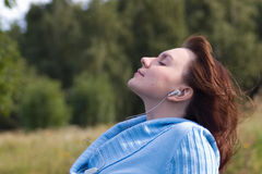 Music dreams. Woman relaxing listening music at a nature Royalty Free Stock Images