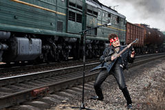 The Music Drive. Man in leather plays guitar on the background of a train whizzing past Royalty Free Stock Photos