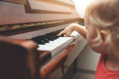 Music education - child pushing piano keys stock photography