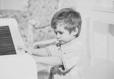 Music education. Child sit near piano keyboard, white background. Kid spend leisure near musical instrument. Boy cute. And adorable puts finger on keyboard of stock image