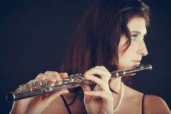 Woman playing transverse flute on black. Music and elegance. Alluring elegant woman playing on transverse flute. Female musician with her instrument performing Stock Images