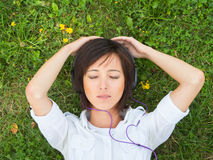 Music enjoyment. Young woman enjoying the music with closed eyes on a summer meadow Royalty Free Stock Photo