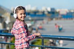 Music everywhere you go. Child listen music outdoors modern headphones. Kid little girl listen song headphones. Music. Account playlist. Customize your music stock image