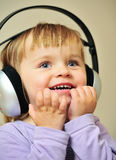 A music fan. A little girl listening to music with her headphones Stock Photography