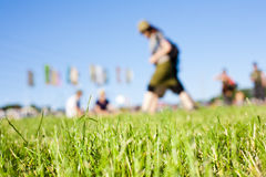 Music Festival Field. Relaxed scene at a summer music festival. Some people sitting on the grass, others exploring the site. Very shallow depth of field Royalty Free Stock Photos