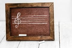 Music figure and treble clef drawn in chalk on a school board. Stock Photo
