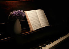 Music flowers. Purple flowers in vase and hymnal open on old piano Royalty Free Stock Photo
