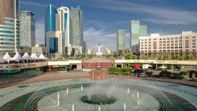 Music fountain and new business district timelapse from bridge in Astana. Music fountain and new business district timelapse with traffic on road from bridge in stock footage