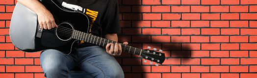 Music - Fragment man play a black acoustic guitar. On a red brick wall background stock photo