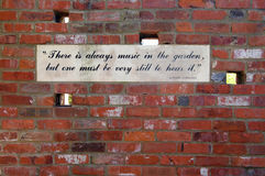 Music In the Garden. A Plaque on an old brick wall in a secret garden There is Always music in the garden but one has to be still to hear it Royalty Free Stock Photo
