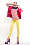 Music girl. Studio shot of young pretty teenage girl with long slender legs wearing colorful casual style clothes like yellow jeans, stripped red top tank, pink Royalty Free Stock Photography